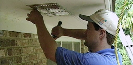 Installing soffit vents in eaves.