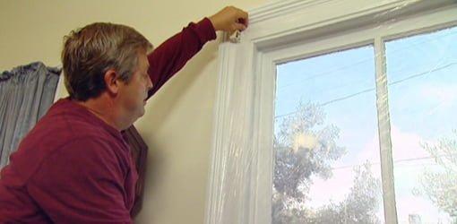 Installing plastic film on window.