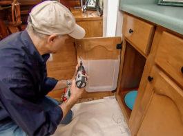 Joe Truini installing plastic container on kitchen cabinet door