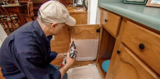 Joe Truini installing plastic container on kitchen cabinet door