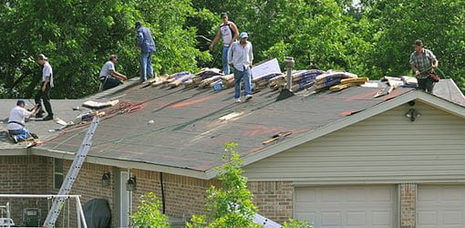 Roofers replacing old roof on house.