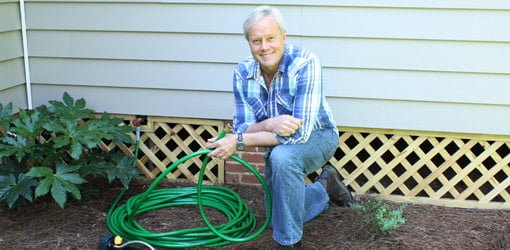 Danny Lipford in yard with hose.