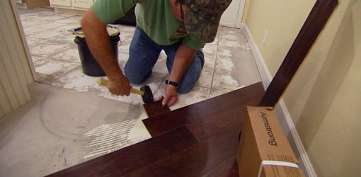 Tapping engineered wood flooring into place with rubber mallet.