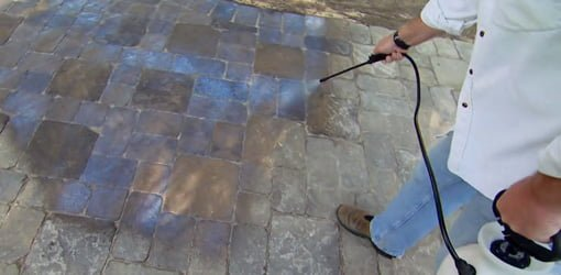 Applying sealer to a paver driveway.