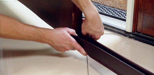 Installing Triple Draft Seal door sweep on bottom of entry door.