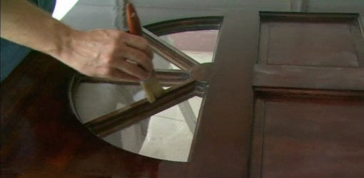Using a paintbrush to apply spar varnish to an entry door.