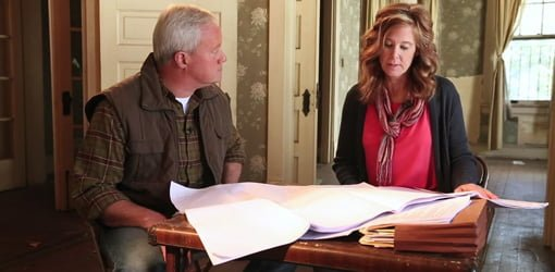Danny Lipford and Esther de Wolde sitting at a card table discussing house renovation plans.