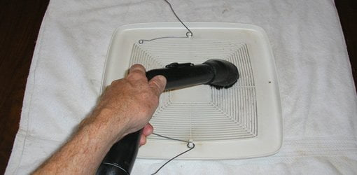 Using a dusting brush on a vacuum to  clean vent fan cover.