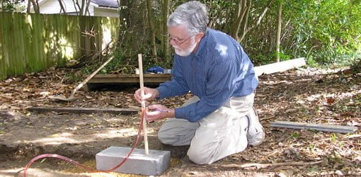 Using a homemade water level to level a shed foundation.
