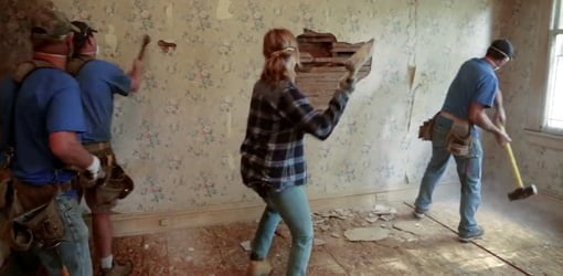 Using a sledgehammer to demolish a plaster wall.