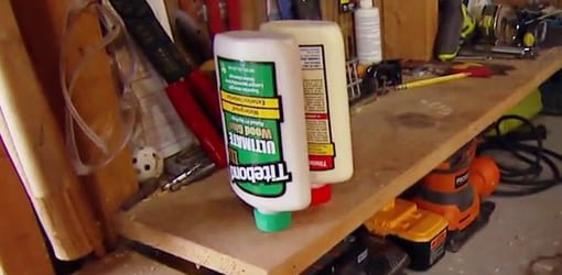 Glue bottle stored upside down in hole drilled in workshop shelf..