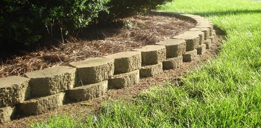 Pine straw mulch behind block retaining wall.