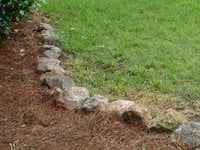 Stones bordering pine straw mulch planting bed.