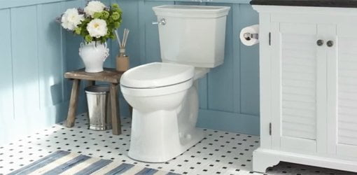 Toilet in blue bathroom with tile floor and flowers.