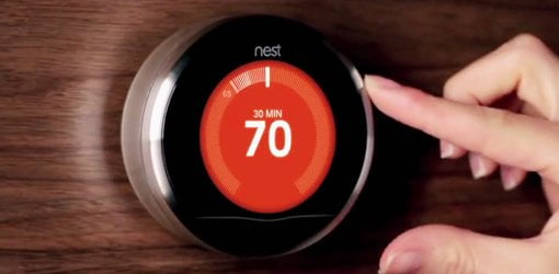 Hand adjusting a Nest Learning Thermostat to 70 degrees.