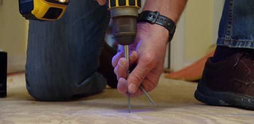 Using a cordless drill to drive screws through a plywood subfloor.