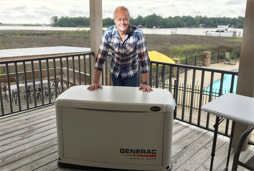 Danny Lipford standing on deck overlooking water with Generac standby generator.