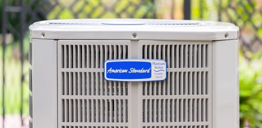 American Standard air conditioner condenser unit, seen outdoors on a bright sunny day