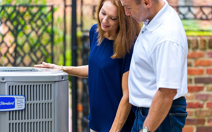 Married couple looks at their American Standard air conditioner and wonders whether it's time to maintain their system