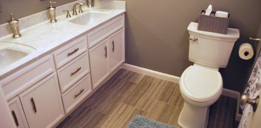 Bathroom with white painted vanity, gray walls, wood look tile floor, and toilet.