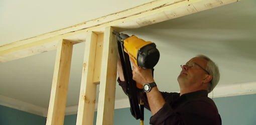 Danny Lipford using a nail gun to frame up the interior wall.