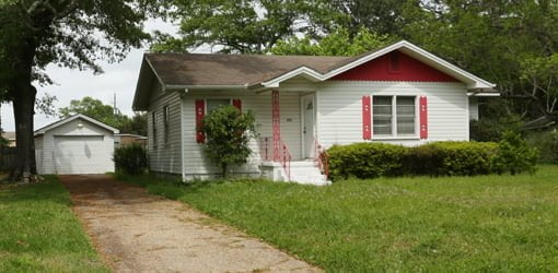 Small white sided house with pink trim.