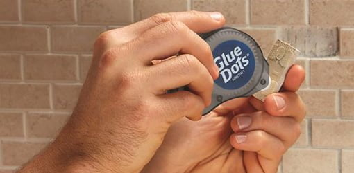 Using Glue Dots to attach a tile to a wall.