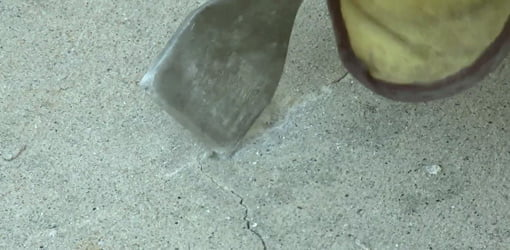 Using a masonry chisel to remove any loose concrete from the crack.