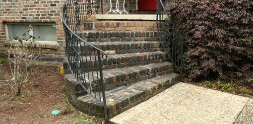 Curved brick porch steps with wrought iron railing on front of house.