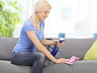 Woman spraying essential oils on sofa.