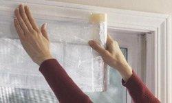 Installing plastic window film on window.