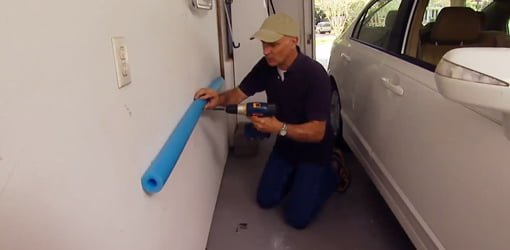 Attaching a pool noodle to the garage wall to keep from damaging car doors.