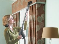 Woman vacuuming drapes with NuTone PurePower central vacuum.