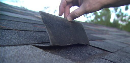 Bending back asphalt roof shingle until it breaks.