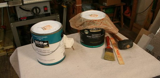 Paint cans sitting on table with and without plastic bag under lid.