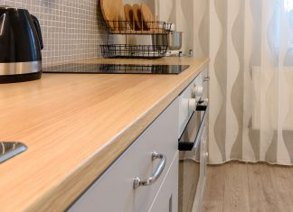 Plastic, melamine-coated cabinets in a modern kitchen with a smooth cooktop.