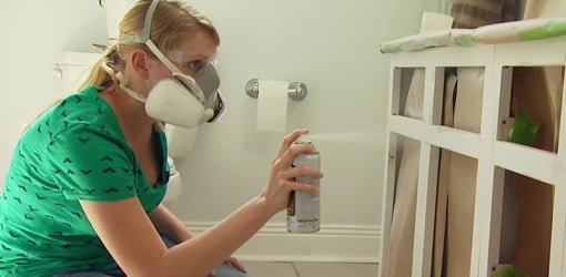 Woman spray painting bathroom vanity.