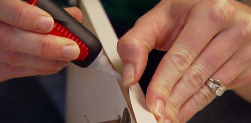 Utilisation de colle instantanée pour refixer le revêtement de mélamine pelable sur l'armoire.