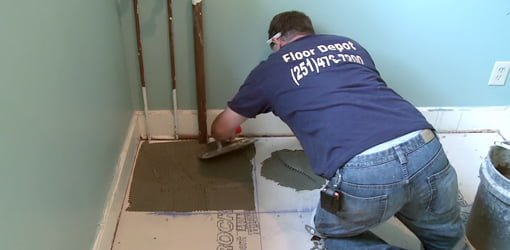 Man in blue shirt laying tile on cement backer board on a plywood subfloor.