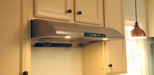 Stainless steel range hood over stove with painted cabinets.