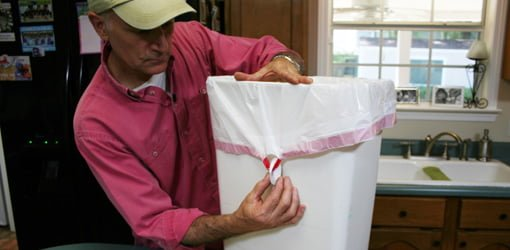 Attaching self-adhesive hooks upside down to hold garbage bag in place.