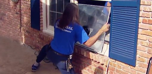 Man in blue shirt removing fogged glass from window frame.