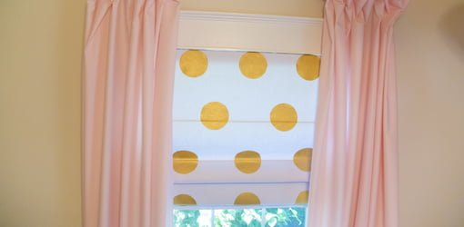 White Roman shade on window with gold painted polka dot decorations.