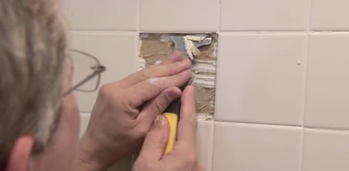 Removing damaged tile from a bathroom tub surround.