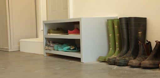 Drop zone shoe cabinet painted gray by garage door.