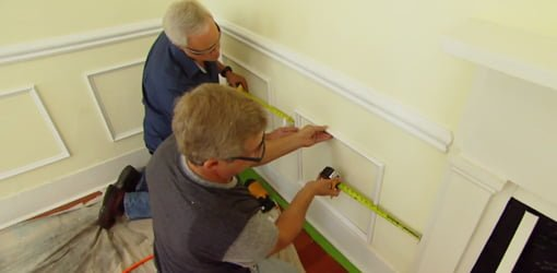 Installing white faux wainscoting on yellow walls in living room.
