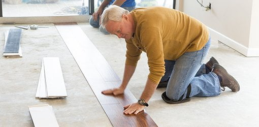 Danny Lipford lays vinyl plank flooring in the beachfront condo.