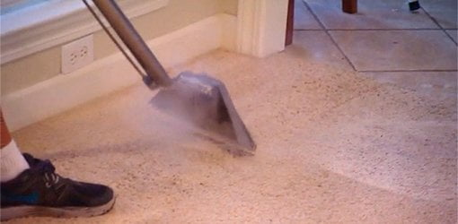 A professional using a carpet steamer.