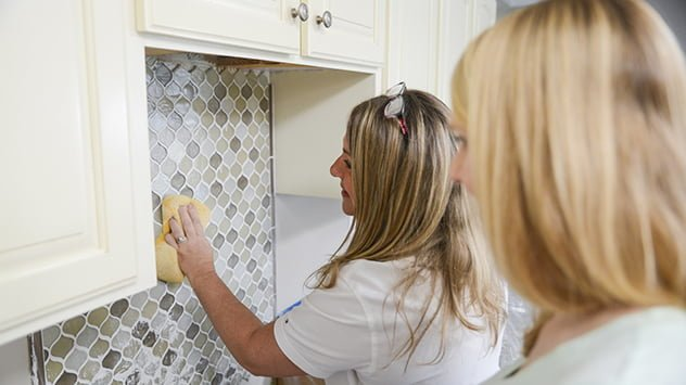 Kym Sigler wipes excess the grout from the tile backsplash.
