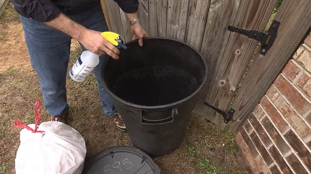 Joe Truini sprays the inside of the trash can with ammonia.